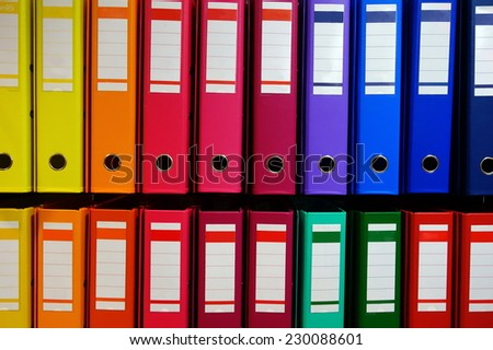 Colorful ordner / document binder stacked on rack in beautiful way - stock photo