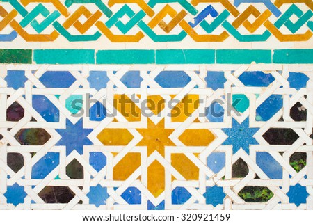 colorful ornate pattern of moorish tile decorations on alhambra wall in andalusia - stock photo