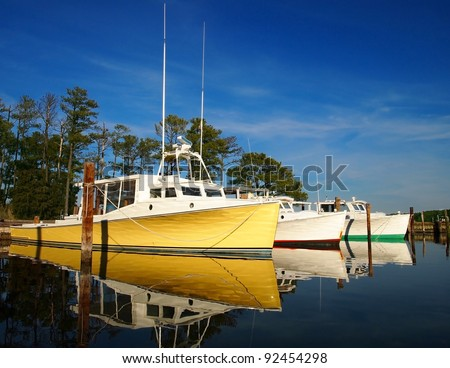 Colorful oyster boats in the water at marina. - stock photo