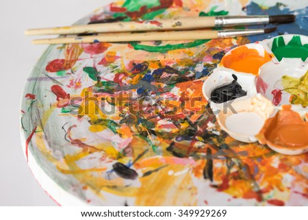 Colorful  paint palette with brushes for art and craft background  - stock photo