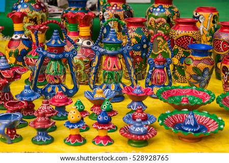 Colorful painted clay vases, lanterns and various decorative items for sale at a street market in India