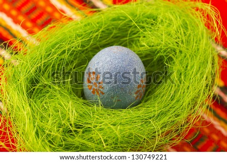 Colorful painted Easter egg in small basket with grass. - stock photo