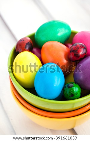 Colorful painted Easter eggs in a bowls