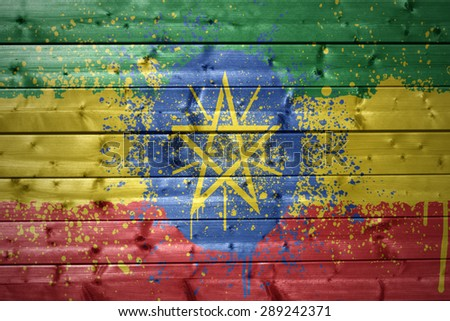 colorful painted ethiopian flag on a wooden texture - stock photo