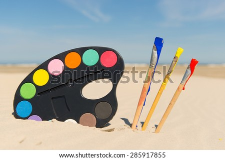 Colorful Painters palette with brushes at the beach - stock photo