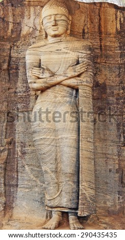 Colorful Painting Stone Carving Giant Standing Buddha Statue in Anuradhapura, Sri Lanka on Canvas Texture - stock photo