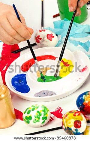 Colorful paints on palette with brushes ready for painting easter eggs. Concept for art and craft classes. - stock photo