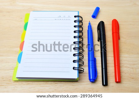 Colorful pan with notebook  on wooden background