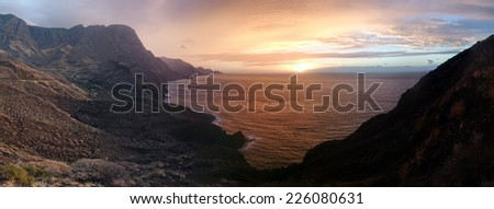 Colorful panoramic sunset or sunrise over a tranquil ocean and coastline on a cloudy day viewed from a headland or mountain peak - stock photo