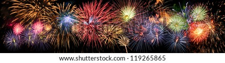 Colorful panoramic view of fireworks over night sky - stock photo