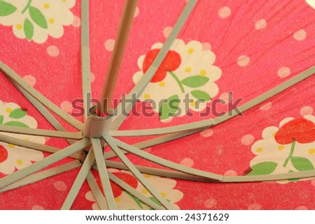 Colorful paper cocktail umbrella or parasol with cherry design - stock photo