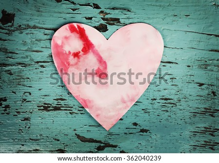 Colorful paper heart on wooden background.
