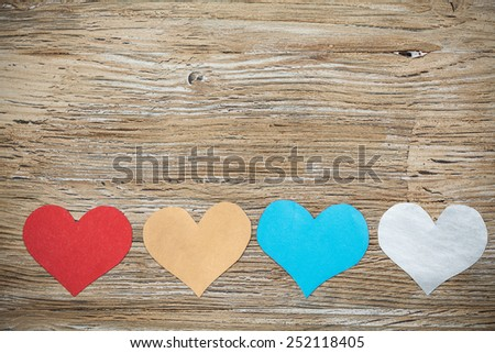 Colorful paper hearts on wood backgrounds. Valentine's Love concept - stock photo