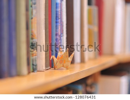 Colorful paper origami crane on the bookshelf with books - stock photo
