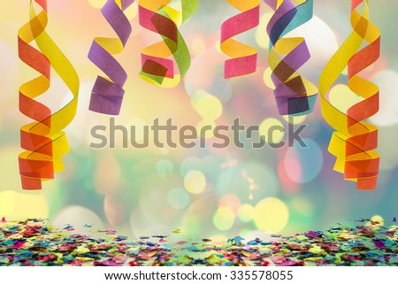 colorful paper streamer hanging from top with confetti on the bottom for celebration - stock photo