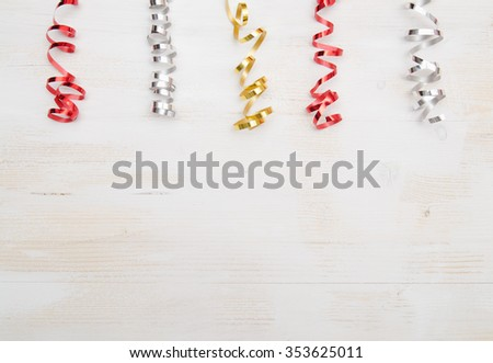 Colorful Paper Streamers on White Wooden Background.  - stock photo