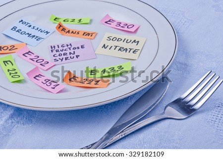 Colorful papers imitating food additives on plate with fork and knife, concept.