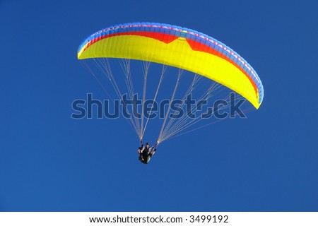 colorful paraglider on blue bright sky - stock photo