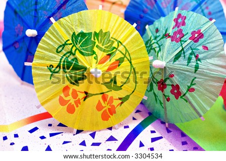 Colorful party drink umbrellas on a festive background paper. - stock photo