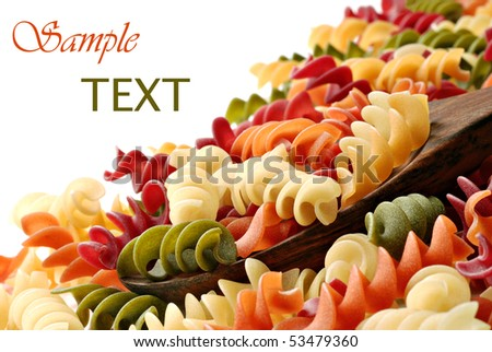 Colorful pasta with wooden spoon on white background.  Copy space included. - stock photo