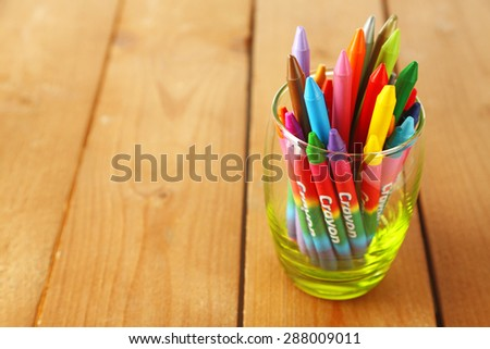 Colorful pastel crayons in glass on wooden background - stock photo