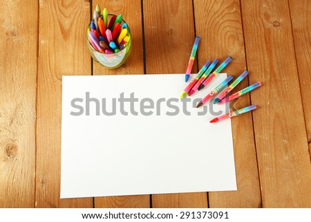 Colorful pastel crayons with white sheet of paper on wooden background - stock photo