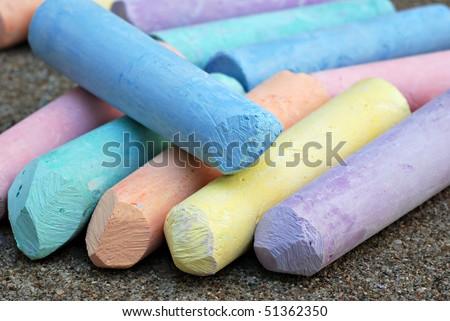 Colorful pastel sidewalk chalk on concrete.  Macro with shallow dof. - stock photo