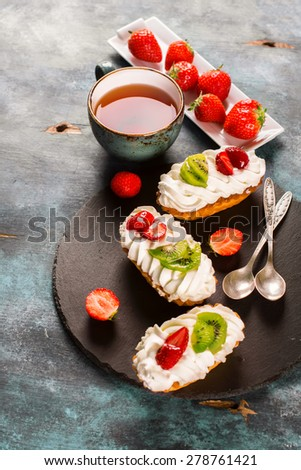Colorful pastry cakes with chantilly cream, fruits and berries on grunge blue wooden background, selective focus - stock photo