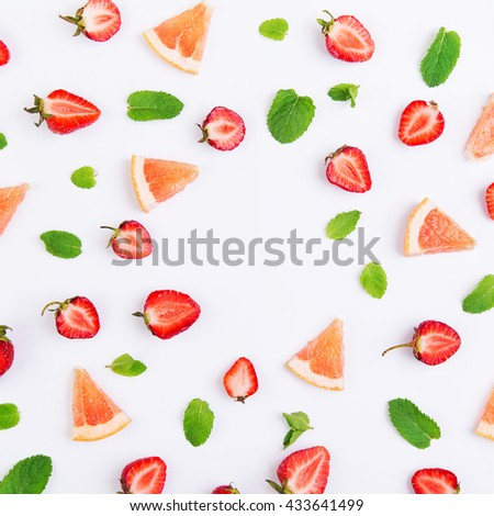 Colorful pattern of strawberry halves, slices of grapefruit and mint leaves on a white background. Top view with copyspace - stock photo