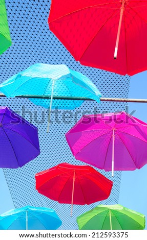 Colorful pattern of umbrellas, parasols  suspended above a street with blue sky as background.  - stock photo
