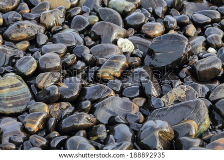 Colorful pebbles touching wave at beautiful rock island, called Koh Hin Ngam, near Lipe island, Thailand