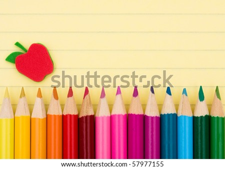 Colorful pencil crayons on a sheet of lined paper, Education background - stock photo