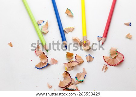Colorful pencil crayons on white desktop with pencil shavings - stock photo