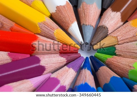Colorful pencils arranged in a circle close up
