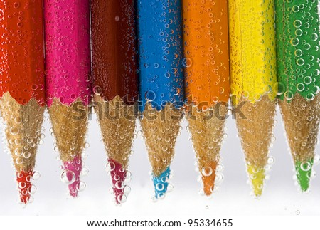Colorful pencils close-up on white background with shallow dof, into water with bubbles. - stock photo