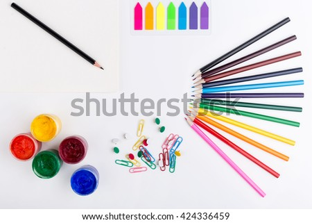 Colorful pencils, gouache paint, stickers, clips and pins on white background