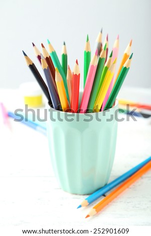 Colorful pencils in cup on white wooden background - stock photo