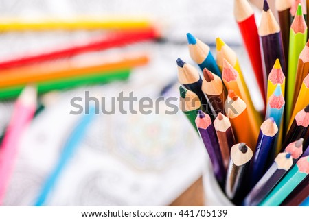 colorful pencils in jar with coloring book in background