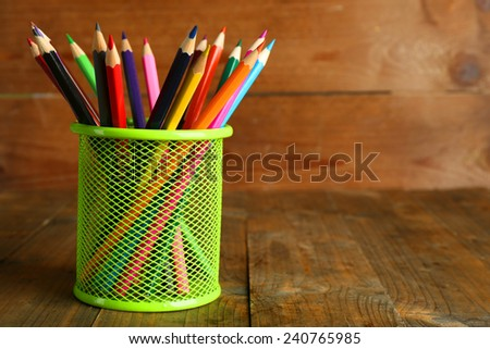 Colorful pencils in metal holder on rustic wooden background - stock photo