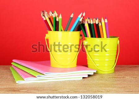 Colorful pencils in two pails with copybooks on table on red background - stock photo