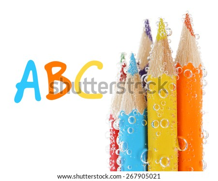 Colorful pencils in water with bubbles, isolated on white - stock photo