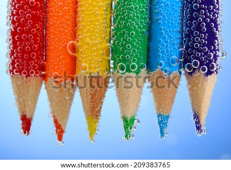 Colorful pencils in water with bubbles on blue background - stock photo