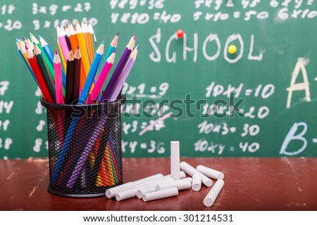 Colorful pencils of red yellow orange violet purple pink green and blue in stationary cup and chalk standing on brown school desk on written blackboard backgroung on lesson of math - stock photo
