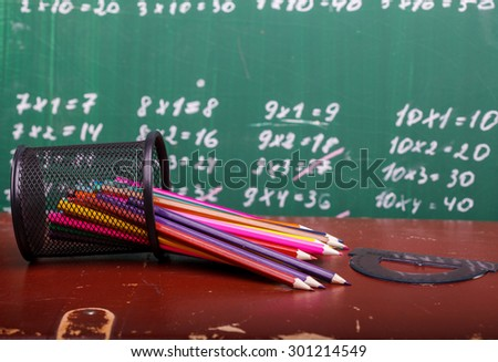 Colorful pencils of red yellow orange violet purple pink green and blue in stationary cup and ruler lying on brown school desk on written with white chalk blackboard backgroung on lesson of math - stock photo