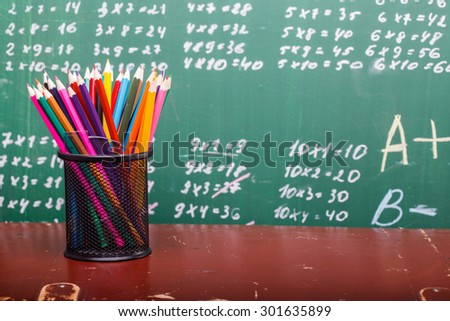 Colorful pencils of red yellow orange violet purple pink green and blue in stationary cup and ruler standing on brown school desk on written with white chalk blackboard backgroung on lesson of math - stock photo