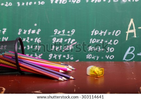 Colorful pencils of red yellow orange violet purple pink green and blue in stationary cup and steel lying on brown school desk on written with white chalk blackboard backgroung on lesson of math - stock photo