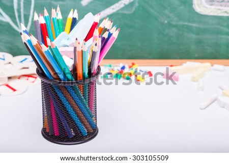 Colorful pencils of red yellow orange violet purple pink green and blue in stationary cup on school desk with white sheet of paper on written with chalk blackboard background, horizontal picture - stock photo