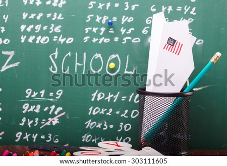 Colorful pencils of red yellow orange violet purple pink green and blue stationary cup ruler fan english alphabet and paper plane with back to school text written with white chalk blackboard on math - stock photo