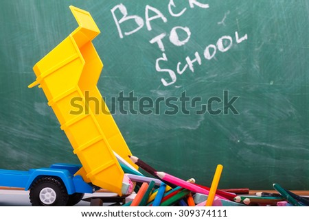 Colorful pencils of red yellow orange violet purple pink green blue chalk and fan english alphabet in plastic truck car toy lying on white school desk on back to school text, horizontal photo - stock photo