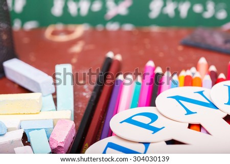 Colorful pencils of red yellow orange violet purple pink green blue ruler chalk and fan english alphabet with capital letters lying on brown school desk on written with white chalk blackboard - stock photo
